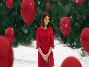 Una mujer con un vestido rojo rodeada de globos rojos