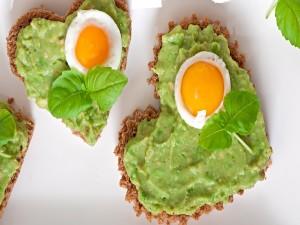 Dos tostadas en forma de corazón con huevos y aguacate