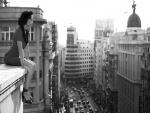 Mujer sentada en el borde de un edificio