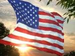 Sol brillando tras la bandera de los Estados Unidos