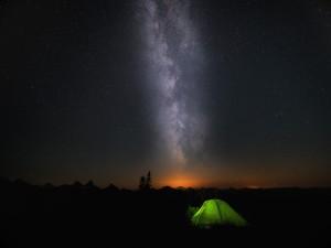 Tienda de campaña verde bajo un cielo estrellado