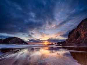 El sol ilumina las montañas y el mar