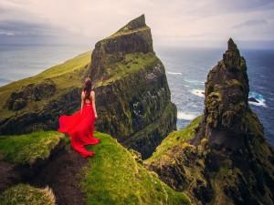 Mujer con vestido rojo sobre un acantilado observando el mar