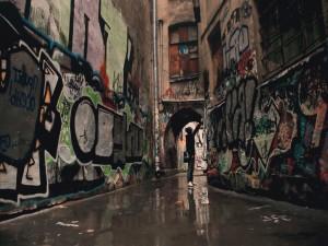 Chico haciendo un graffiti en un callejón