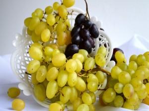 Uvas verdes y negras en un recipiente