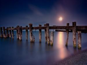 Al atardecer el sol ilumina los soportes de madera en el mar