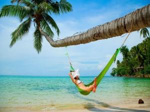 Mujer descansando en una hamaca en la playa