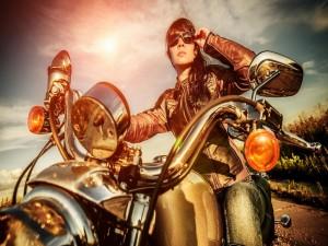 Chica con chaqueta de cuero y gafas de sol sentada en una moto