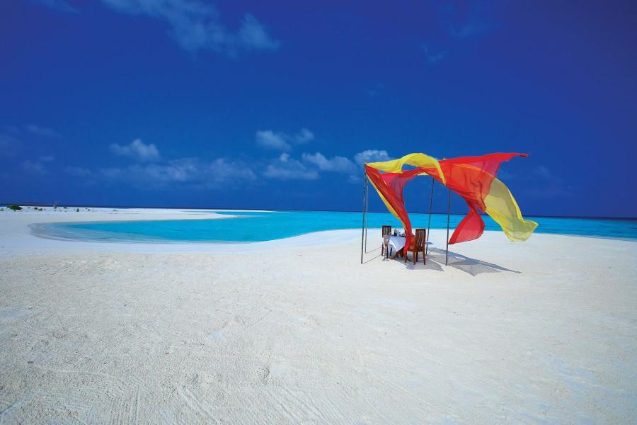 Comida romántica en una playa de arena blanca