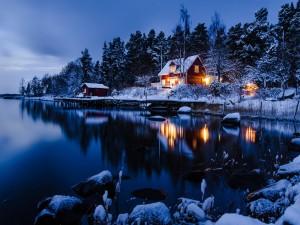 Cabaña nevada junto a un lago