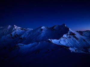 Montañas cubiertas de nieve bajo el cielo nocturno