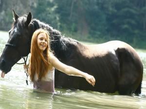 Una mujer y su caballo caminando en el agua