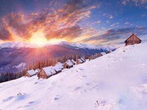 Sol iluminando las cabañas nevadas