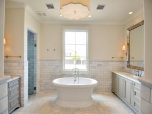 Amplio cuarto de baño de mármol con una bañera en el medio