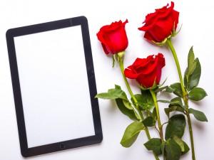Una tablet y un ramo de rosas rojas