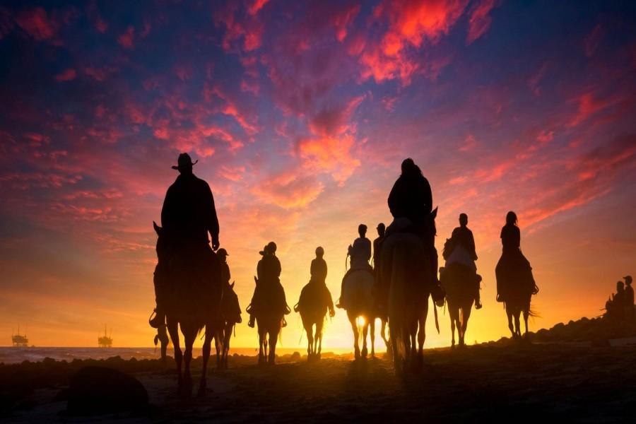 Jinetes a caballo en la puesta del sol