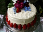 Pastel con crema blanca decorado con fresas y flores